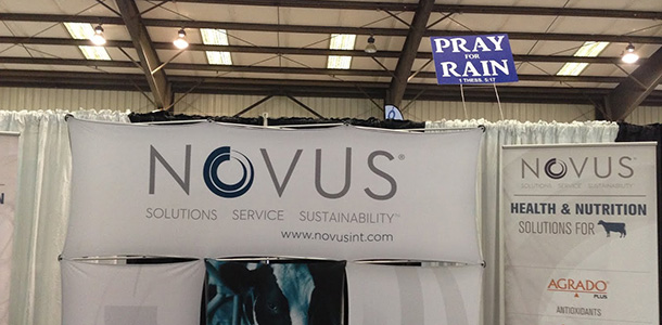 world ag expo novus booth pray for rain sign