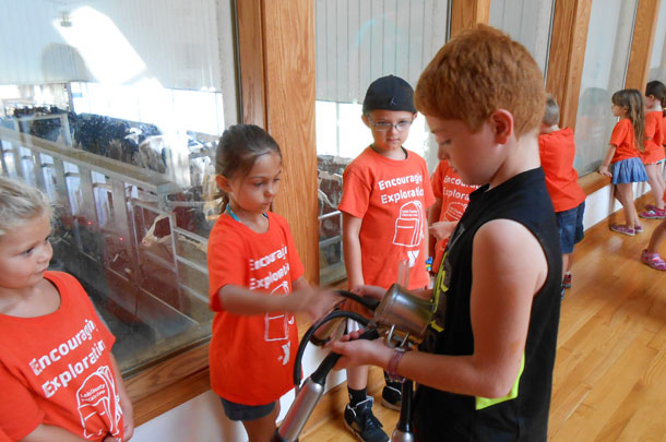 Jack Hastings showing kids a milking machine